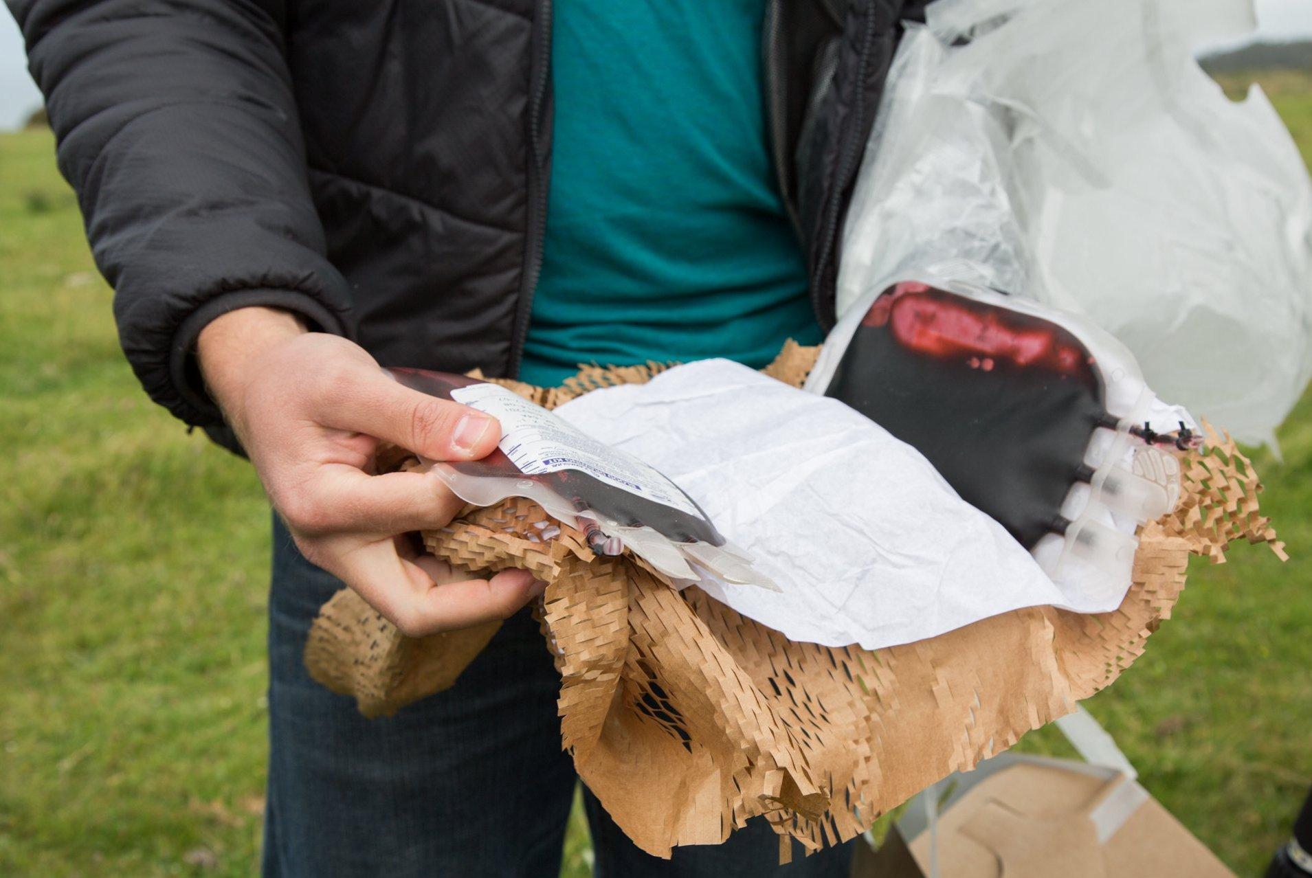 [Foto: Pendiri Zipline, Keenan Wyrobek, membuka paket yang baru dijatuhkan drone dalam sebuah penerbangan uji coba | Melia Robinson via techinsider.io]